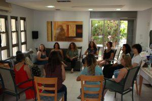 נשים יושבות במעגל על כיסאות עץ בהדרכה של רעות רסלר
