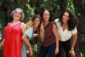 קבוצת נשים עם רקע עצים ירוקים צוחקות מכל הלב
